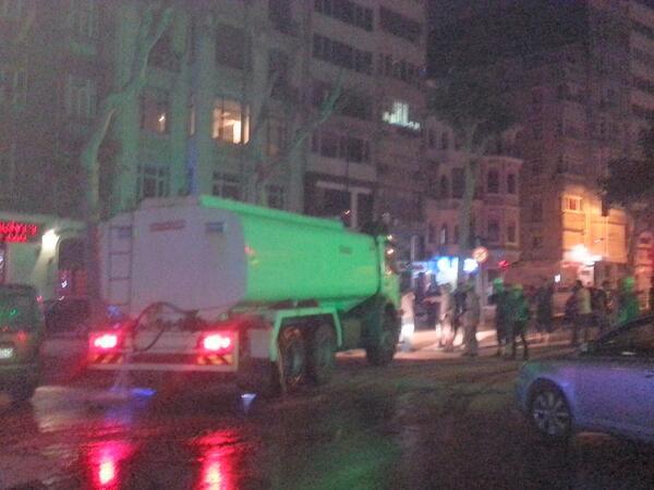 Νέοι στέκονται μπροστά στο βυτιοφόρο που θα μεταφέρει νερό στα οχήματα της αστυνομίας.Αναγκαστικά χύνει το νερό του.